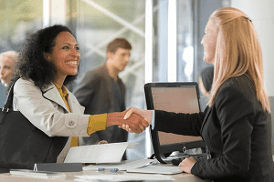 Adviser and customer exchanging a handshake at the car rental desk